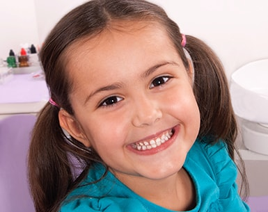 Young girl with brown hair and pigtails smiling