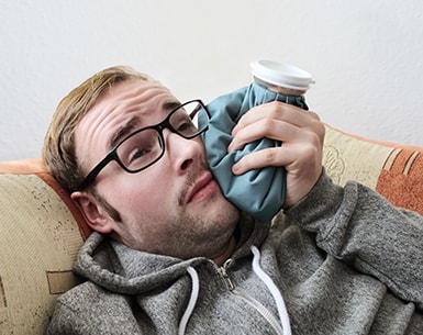 Man holding an ice pack to the side of his jaw while laying on a couch