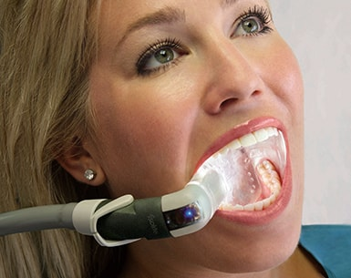 Dental patient opens her mouth for dental exam with a light to see her teeth