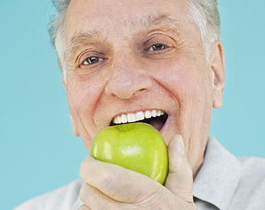 Elderly man eating green apple with white teeth.