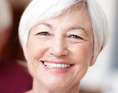 Older woman with short white hair smiling