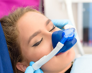 Woman with sedation gas mask on for dental procedure