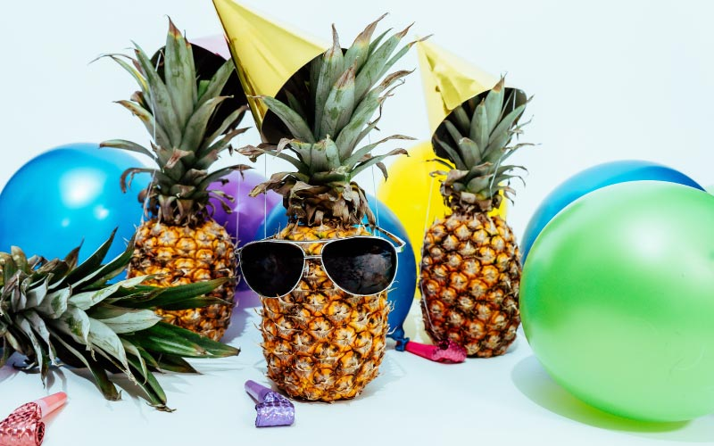 Cluster of pineapples with yellow party hats, noise makers, balloons, and a pair of black sunglasses