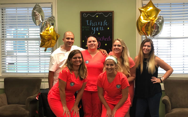 Dr. Quiros and his dental team pose in coral scrubs next to decorations celebrating 100+ Google reviews